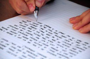 Student writing an essay to register for a Duke summer program.