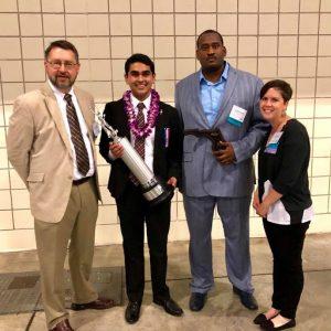 A student along with his mentors receiving an award at NSDA